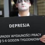 """Zdjęcie przedstawia mężczyznę, który jest pomalowany na twarzy na czarno-biało, na głowie ma kapelusz, w rękach trzyma karton z napisem """"depresja. Spadek wydajności pracy 5-6 godzin tygodniowo""""."""