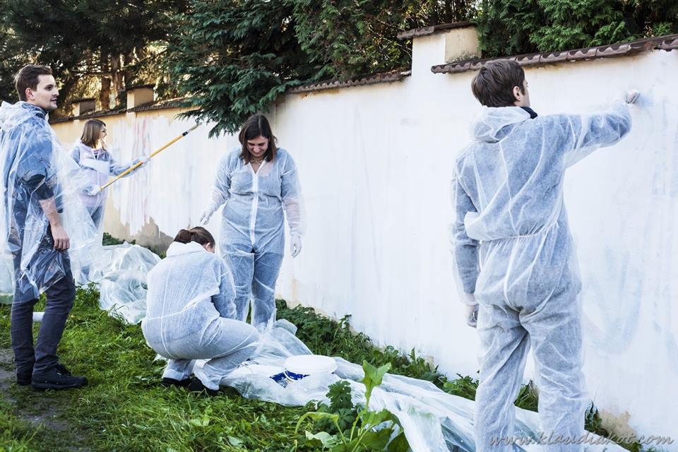 Obrazek przedstawia ludzi zamalowujących na biało mur.