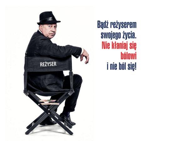 Na zdjęciu znajduje się Jerzy Stuhr, siedzi na krzesłku z napisem reżyser, obok niego znajduje się napis Badź reżyserem swojego życia. Nie kłaniaj się bólowi i nie ból się!