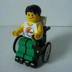 Zdjęcie przedstawia ludzika lego na wóżku inwalidzkim. Ma czarne włosy, biały tshirt oraz zielone spodnie.