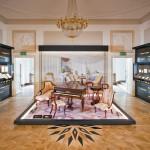 Zdjęcie przedstawia wnętrze sali ekspozycyjnej, na środku na podeście stoi fortepian, wokół niego ozdobne krzesła z epoki oraz szezlong. Pod ścianami stoją gabloty z eksponatami oraz multimedialnymi wyświetlaczami.