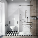 Zdjęcie przedstawia aranżaje łazienki przystosowanej dla niepełnosprawnych - z lewej strony znajduje się toaleta, odzielona ścianką od części z prysznicem i uwywalką, W obu przestrzeniach znajdują się wsporniki do podparcia na ręce.