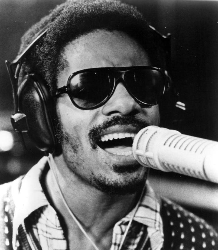 Czarnobiałe zdjęcie przedstawia Stevie'go Wondera śpiewającego do mikrofonu. Na głowie ma duże słuchawki i czarne okulary.