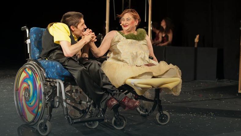 Zdjęcie przedstawia scenę, na której znajduje się dwoje aktorów mężczyzna oraz kobieta na wózkach.