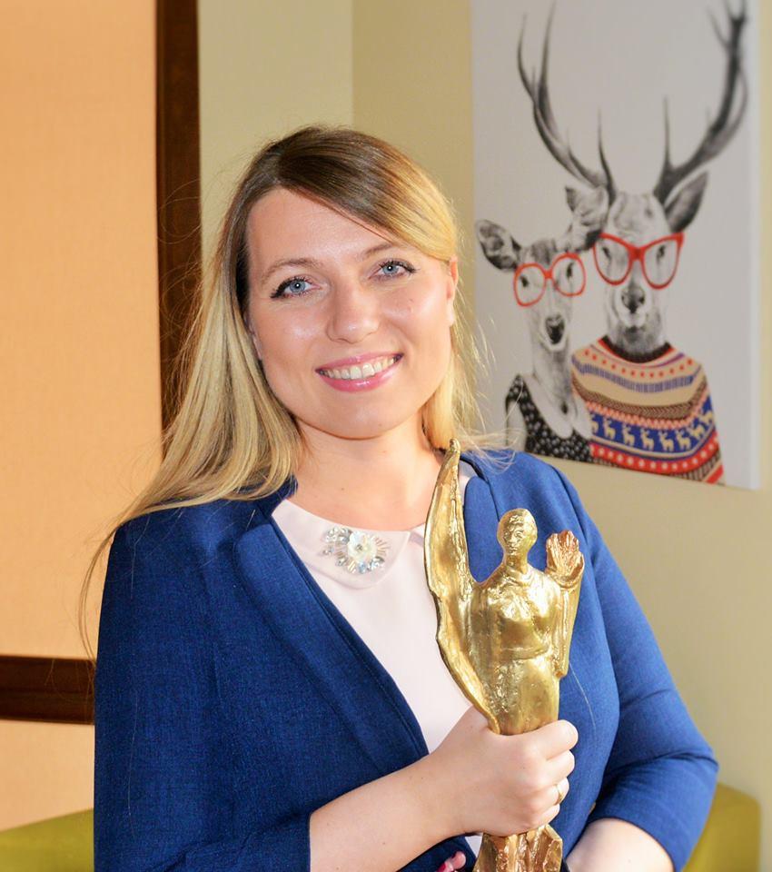 Zdjęcie przedstawia Paulnę Gruszecką trzymającą w ręku statuetkę wręczanom laureatkom konkursu Lady D. Paulina ma długie, proste, blond włosy, uśmiecha się.