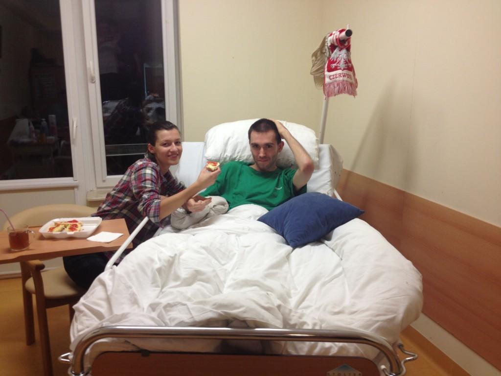 Zdjęcie przedsawia Bartka leżącego w łóżku, oob siedzi przy nim siostra. Oboje się uśmiechają, Ola podaje Bartkowi kanapkę.
