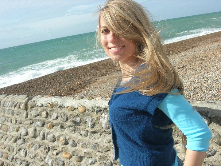 Zdjęcie przedstawia Paulinę Gruszecką stojącą na plaży. Paulina uśmiecha się, patrzy w obiektyw, ma długie, rozwiane przez wiatr włoscy.