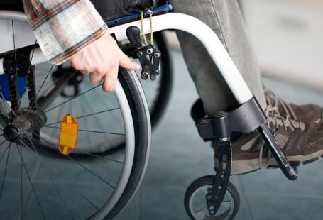 Na zdjeciu widac kadr osoby - ężczyzny siedzącego na wózku inwalidzkim. Widoczna jest tylko głoń trzymająca koło, buty oraz łydka.
