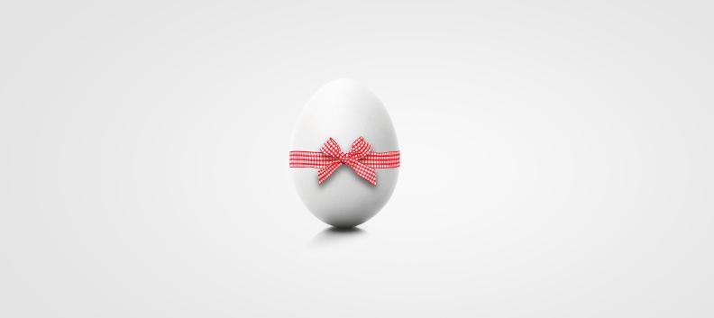 Zdjęcie przedstawia jajko obwiązane wstążeczką w kratkę.