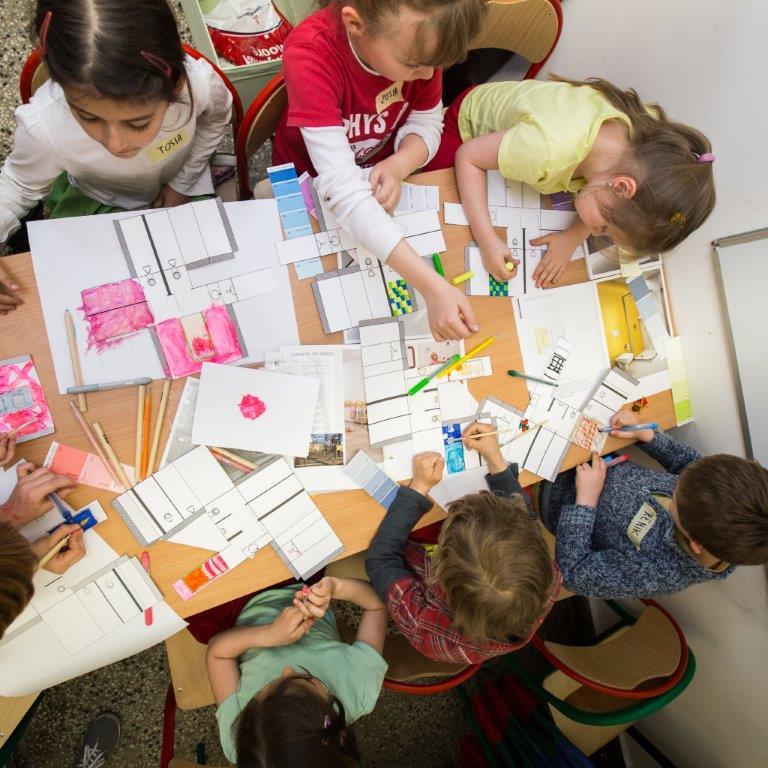 Zdjęcie zrobione jest z góry i przedstawia dzieci projektujące łazienki.