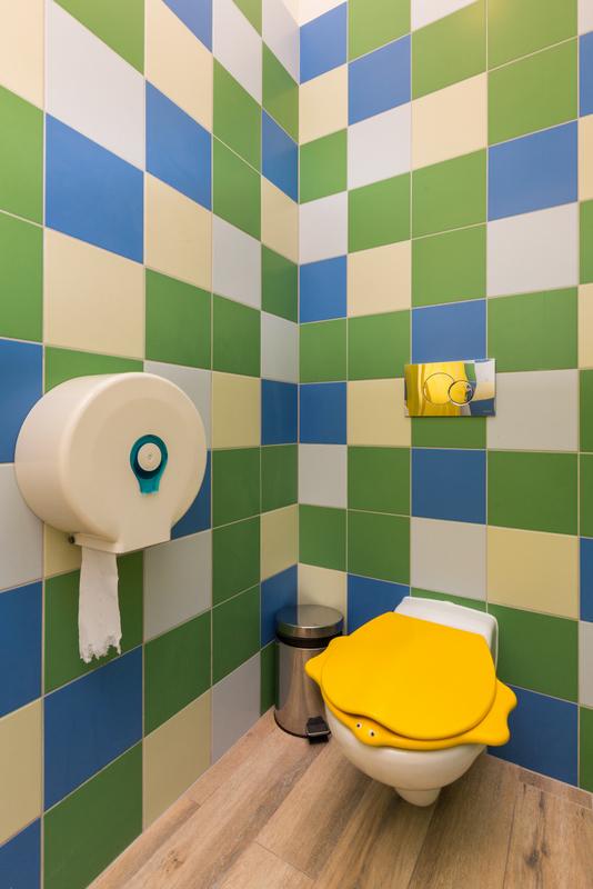Zdjęcie przedstawia łazienkę wykonaną wg projektów dzieci. Na ścianie znajdują się kolorowe kafelki (żółto - biało - zielono - niebieske). Na misce WC znajduje się żółta deska sedesowa w organicznym, przypominającym żółwia kształcie.
