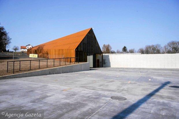 Zdjęcie przedstawia Budynek Muzeum z zewnątrz. Ma prosty kształt wiejskiej chaty ze spadzistym dachem.