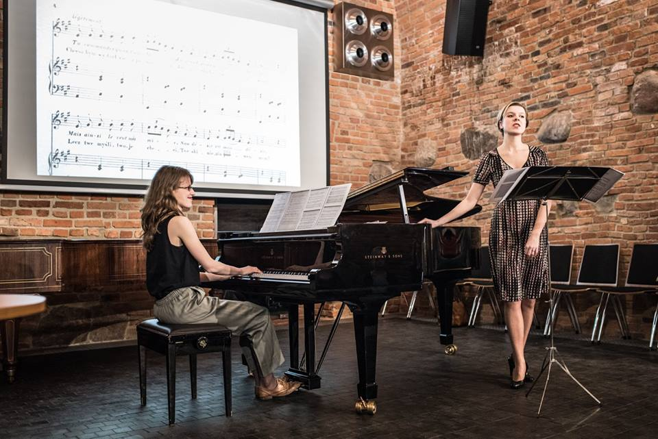 Zdjęcie przedstawia dwie dziewczyny, jedna gra na fortepianie, druga stoi obok i śwpiewa.