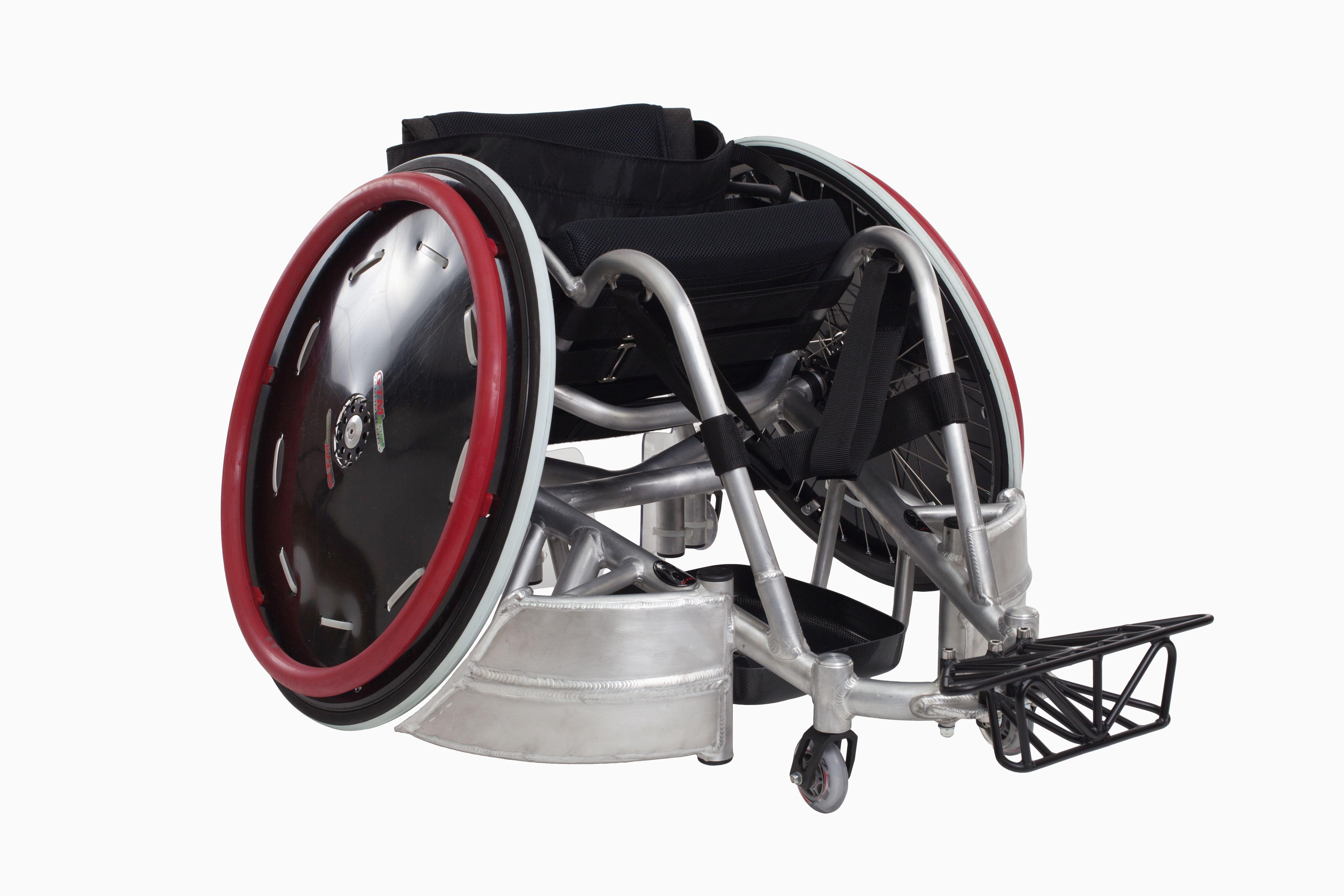 """zdjęcie przedstawia wózek sportowy, do grania w rugby. ma pochlone w pionie koła do wewnątrz, a przy podłodze metalowe """"orchaniacze""""."""