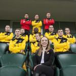 Zdjęcie przedstawia prezeskę klubu wraz z drużyną siedzącą na trybynach. Pani Patrycja siedzi z przodu, za nią w dwóch rzędach siedzą piłkarze, w trzeciam stoją bramkarze i pomiędzy nimi piłkarz.