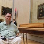 Zdjęcie zrobione w Luwrze. Mężczyzna siedzi na wózku a za nim w tle naścianie wisi Mona Lisa.