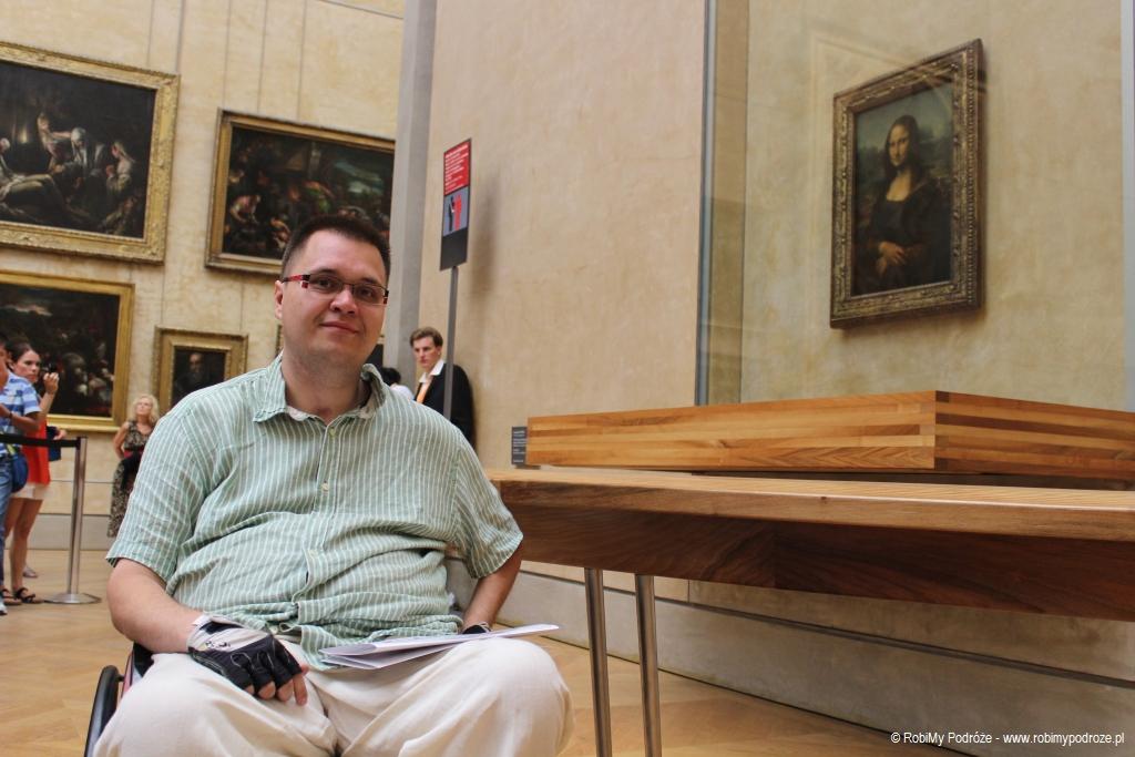 Zdjęcie Pana Kamila zrobione w Luwrze. Mężczyzna siedzi na wózku a za nim w tle na ścianie wisi Mona Lisa.