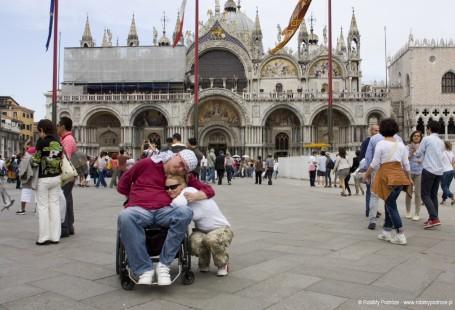 Zdjęcie przedstawiwa panią Małgorzatę z mężem w Wenecji na Placu św. Marka przed katedrą.