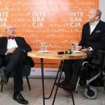 Na zdjęciu z lewej strony na krzesle siedzi Korwin - Mikke, z prawej na wózku siedzi Pawłowski. Pomiędzy nimi znajduje się stolik, na nim szklanki z wodą oraz mikrofon. Za nimi znajduje się baner z logotypem Integracji.