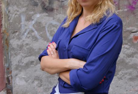 Na zdjęciu znajduje się Karolina Więkiewicz. Ma rozpuszczone blond włosy do ramion, patrzy sie w obiektyw i lekko uśmiecha. Ubrana jest w granatową sukienkę, stoi na tle szarej, zniszczonej ściany.