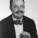 Zdjęcie przedstawia jaśniewielmożnego redaktora Filipa, w okularach, muszce, eleganckiej marynarce, trzymającego laskę (drewnianą).