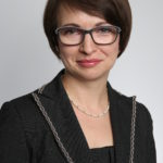 Zdjęcie to portret dr Ewa Dawidziuk, Dyrektor Zespołu do spraw Wykonywania Kar z biura RPO. Pani Dawidziuk ma ciemne, krótkie włosy, okulary w grubych, ciemnych oprawkach. Lekko się uśmiecha, jest ubrana w czarną bluzkę i marynarkę.