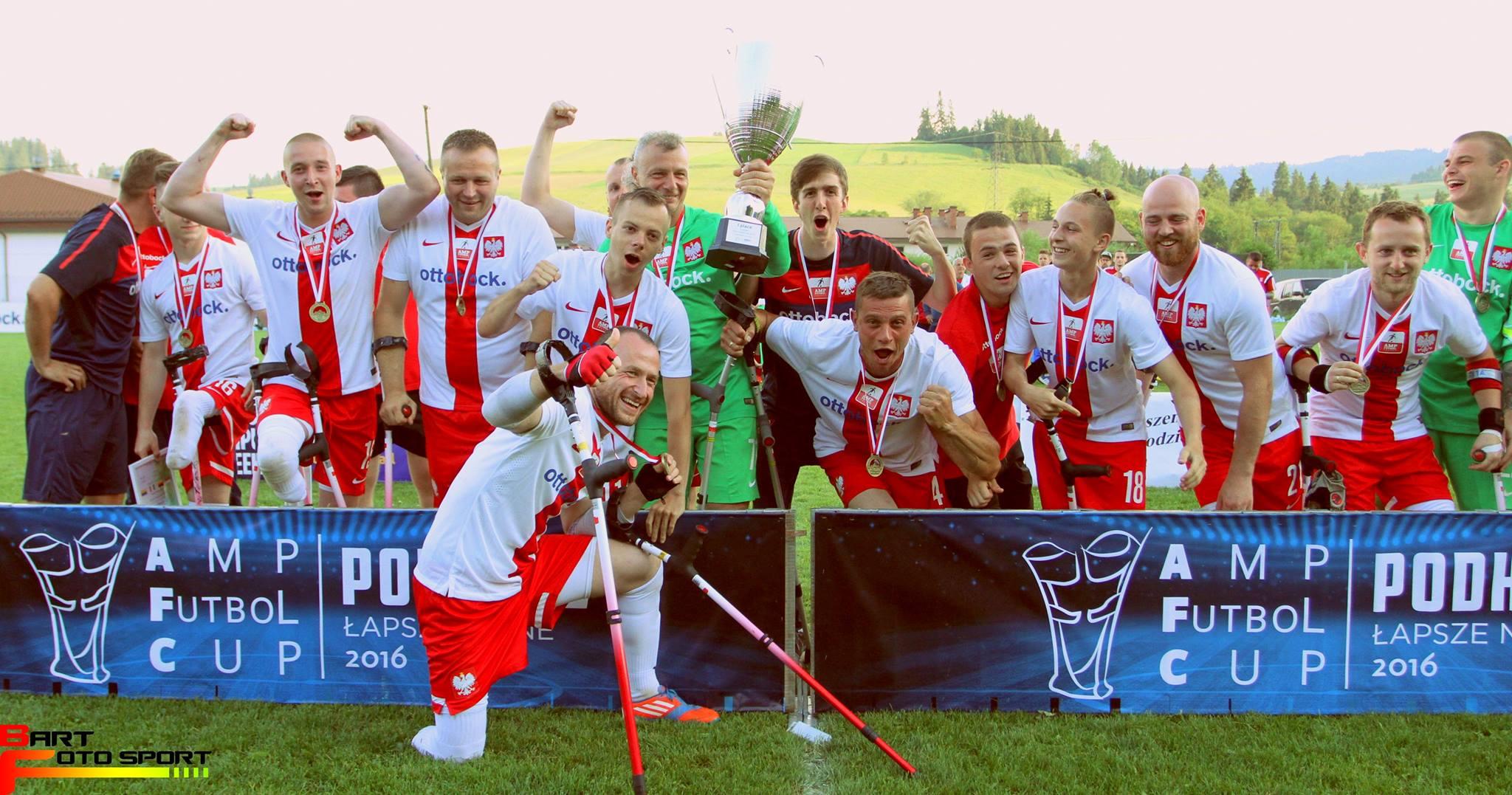 Zdjęcie przedstawia polską drużynę cieszącą się ze zwycięstwa w amp futbolowym turnieju. Zawodnicy cieszą się, jeden z nich ma w ręku puchar.
