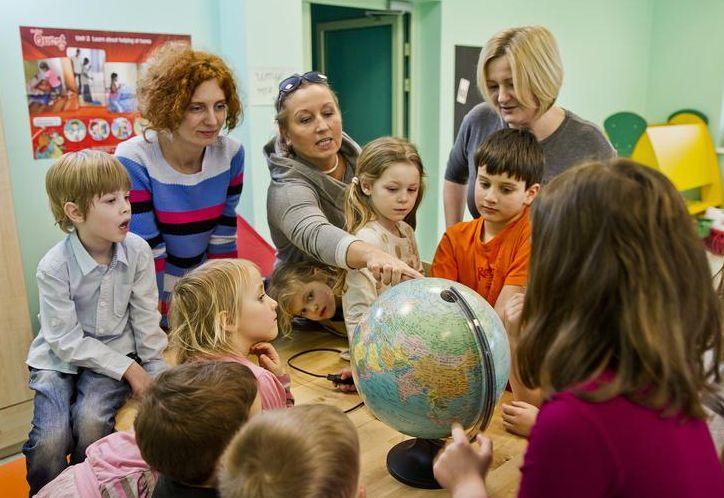Zdjęcie przedstawia dzieci oraz nauczycielki stojące wokół globusa. Są trzy panie i 8 dziecie, wszystkie patrzą się na globus, jedna z pań wskazuje konkretne miejsce na nim.