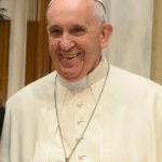 Zdjęcie portretowe papieża. Ma na nim białe szaty, okrągłą, papieska czapeczkę, oraz duży wiszący na piersi krzyż. Papież szeroko się uśmiecha, kadr jest ucięty na wysokości łokci.