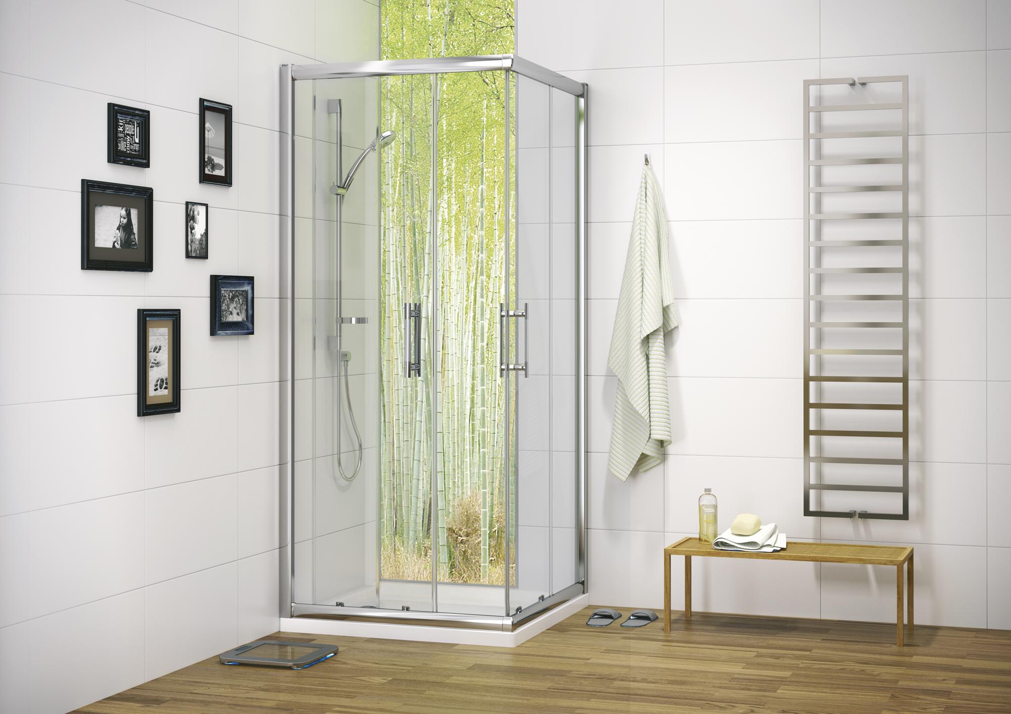 Render przedstawia wnętrze łazienki z kabiną prysznicową Koło Geo 6 Easy. Kabina znajduje się w lewym rogu łazienki, na krótszej ścianie po lewej wiszą czarno-białe fotografie w czarnych, grubych ramkach. Po prawej stronie na ścianie wisi ręcznik, na podłodze stoi mała ławeczka, a na ścianie znajduje się grzejnik. Podłoga jest wykonana z drewnianych paneli.