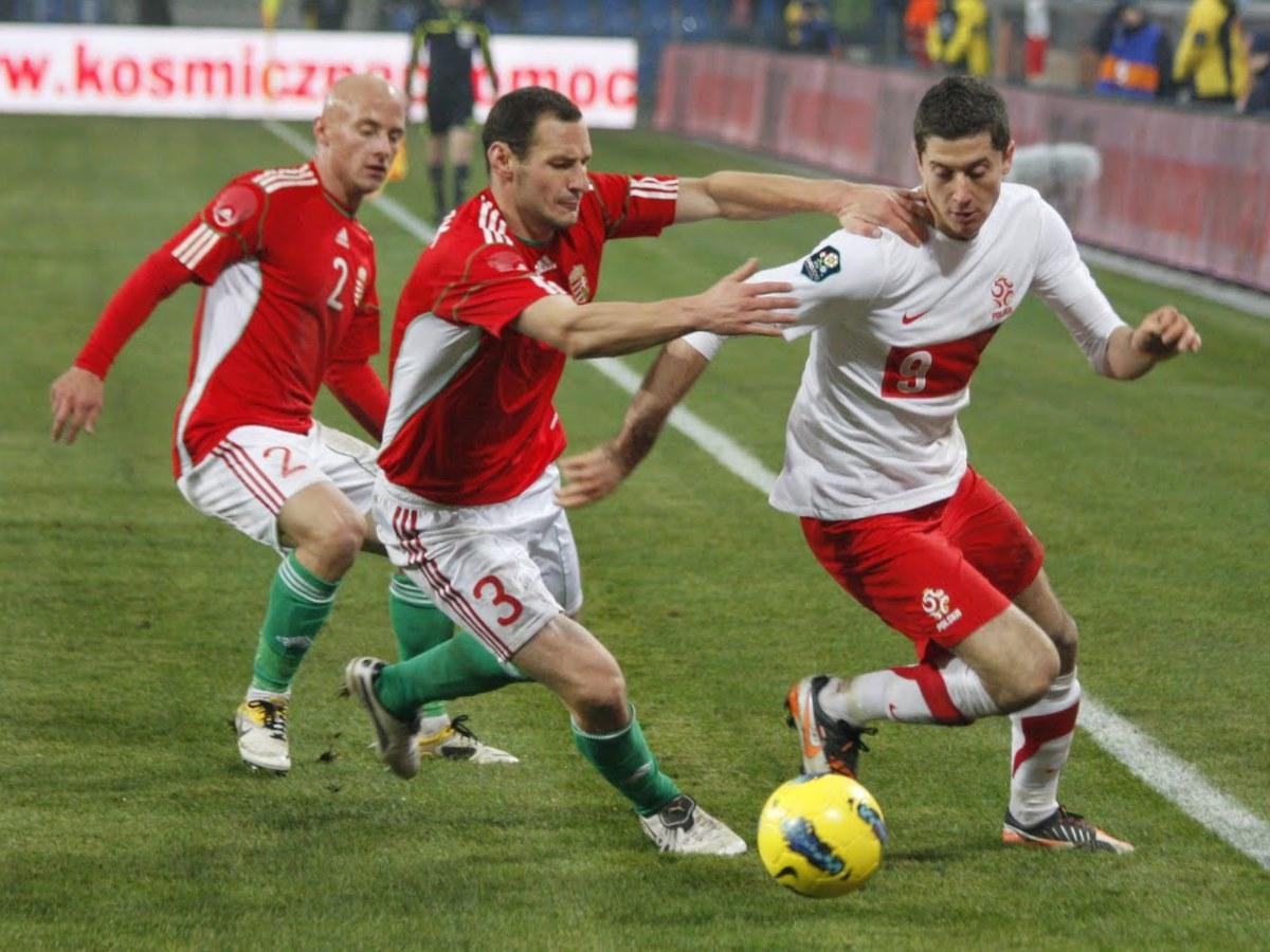 Zdjęcie przedstawia Roberta Lewandowskiego w meczu z Węgrami. Lewandowski prowadzi piłkę, a węgierski zawdnik chce mu ja odebrać.
