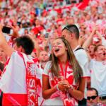 Zdjęcie przedstawia polkich kibiców na trybunacna meczu. Wszyscy się cieszą, trzymają ręce w górze, mają biało-czerwone szaliki.