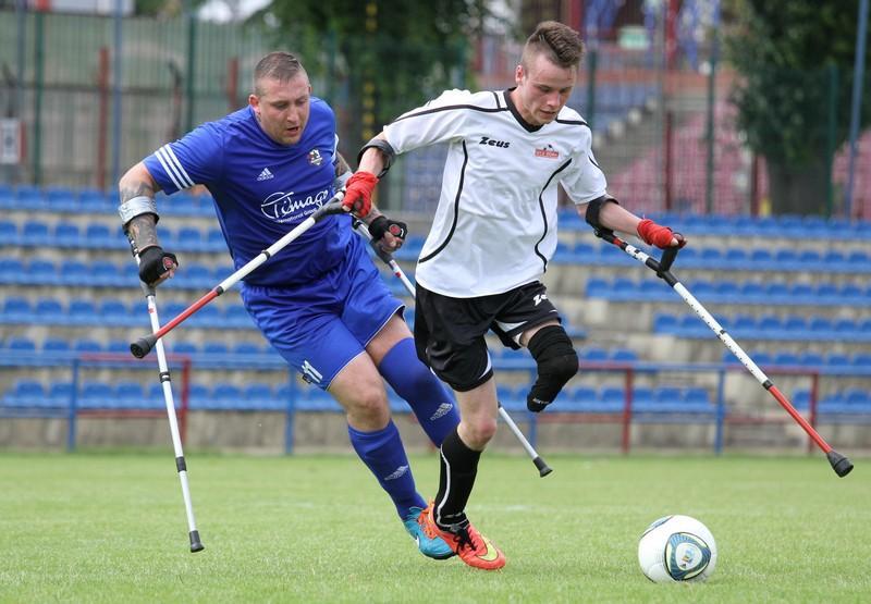 Zdjęcie przedstawia dwóch zawodników na boisku walczących o piłkę. Jeden w białej koszulce jest na przedzie, przed nim znajduje się piłka, drugi w niebieskim stroju jest za nim.