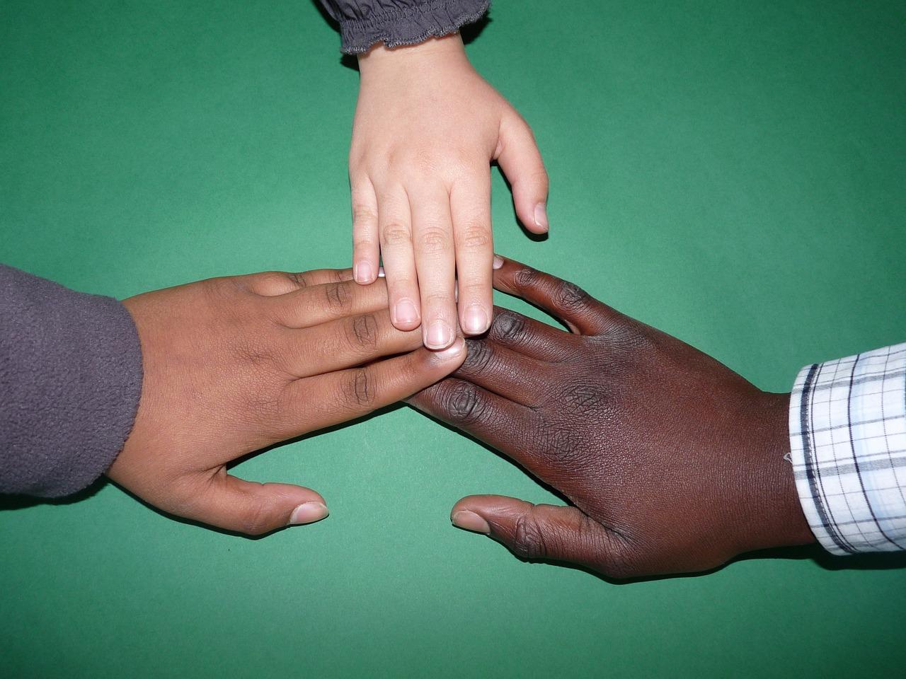 zdjącie przedstawia 3 dziecięce dłonie o różnych kolorach skóry