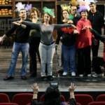 Zdjęcie przedstawia aktórów na scenie, większość z nich stoi, ma rozłożone lub wyciągnięte do góry ręce. Przed nimi na widowni siedzi reżyser.