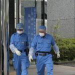 Zdjęcie przedstawia dwóch japońskich ratowników, wychodzących ze szpitala. Obok stoi policjant.