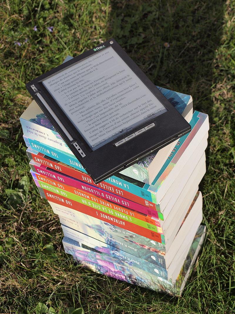 Zdjęcie przedstawia stos książek, ok 15 sztuk ułożonych jedna na drugiej. Na samej górze znajduje się czytnik ebooków. Książki leżą na trawie, mają kolorowe grzbiety.