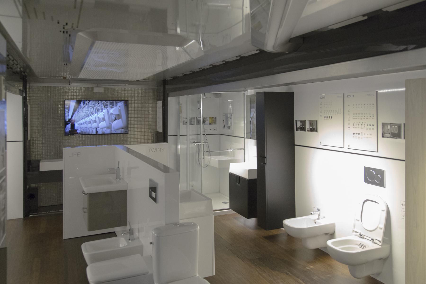Zdjęcie przedstawia wnętrze Promo Trucka Koło. Znajdują się w nich różne produkty - umywalki, miski toaletowe, w rogu znajduje się kabina prysznicowa.
