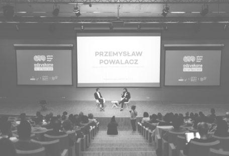 Zdjęcie przedstawia Przemysława Powalacza, udzielającego wystąpienia na Gdynia Design Days. Powalacz siedzi na scenie, na podwyższeniu w sali konferencyjnej, obok niego prowadzący. Za nimi na ścianie znajdują się 3 ekrany rzutnika. Na największy na środku znajduje się napis Przemysław Powalacz, na dwóch mniejszych po bokach znajduje się logo GDD.