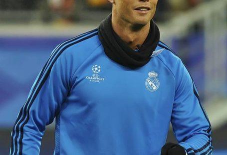 Zdjęcie przedstawia piłkarza na boisku, ubranego w niebieską bluzę.