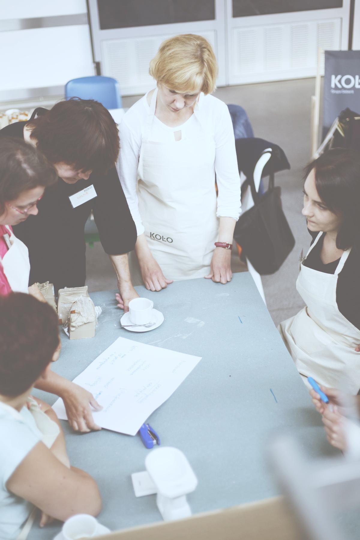 Zdjęcie jest robione lekko z góry, przedstawia osoby biorące udział w warsztatach zgromadzone wokół stołu, na którym leży zapisana kartka papieru, filiżanka po kawie. Uczestnicy maja na sobie fartuchy z logiem Koło.