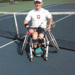 Zdjęcie przedstawia Kamila Fabisiaka na korcie tenisowym