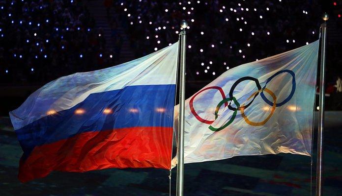 Zdjęcie przedstawia flagę Rosji z lewej strony oraz flagę olimijską z prawej. Flaga Rosi jest podzielona na 3 poziome, równe pasy, od góry biały, niebieski, czerwony. Flaga olimpijska to 5 kółek splecionych ze sobą - 3 u góry, dwa u dołu. Na białym tle.