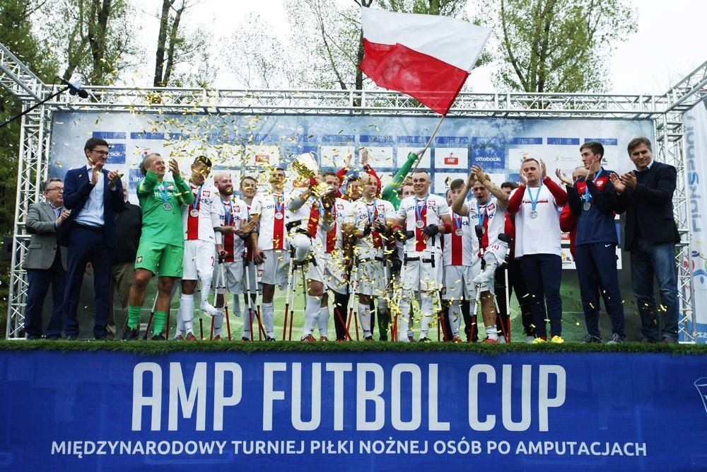 Zdjęcie przedstawia zawodników na postumencie, trzymających puchar i polską flagę podczas Amp Futbol Cup 2015