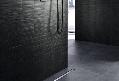 Zdjęcie przedstawia ciemną, grafitową, minimalistyczną łazienkę, z prawie niewidocznym zastosowaniem eleganckiego Geberit Clean Line.