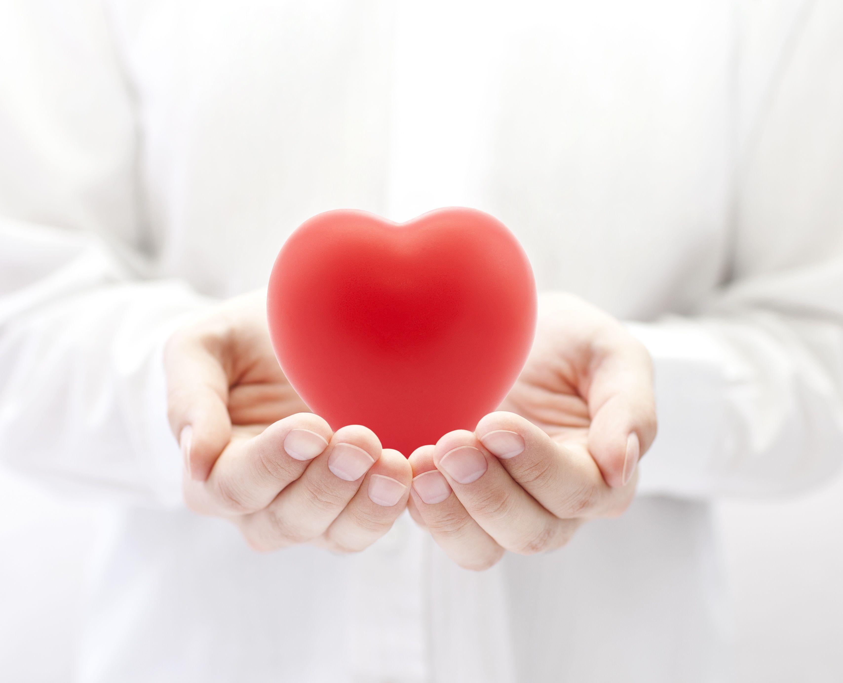 Zdjęcie przedstawia otwarte dłonie podające odbiorcy serce, symbol przekazywanego organu.