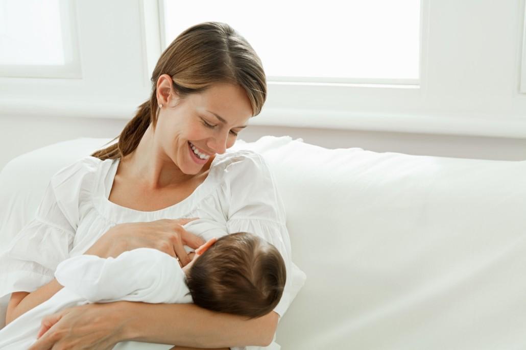 Zdjęcie przedstawia szczęśliwą matkę, karmiącą dziecko piersią.