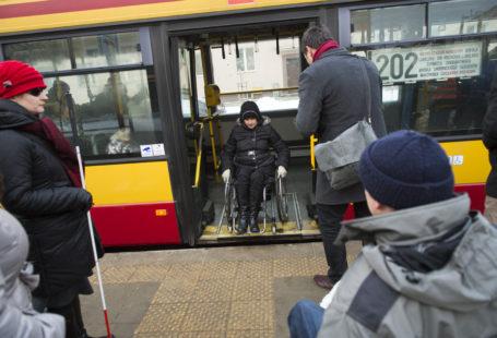 Zdjęcie przedstawia osobę na wózku wyjeżdzającą z autobusu na chodnik.