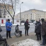 Zdjęcie przedstawia grupę ludzi na przystanku, w tym osób z niepełnosprawnością dyskutujących nad formą ścieżek.