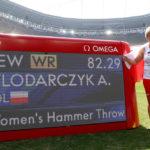 Szczęśliwa Anita Włodarczyk z polską flagą, przy telebinie wyświetlającym jej rekord świata.